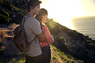 South Africa, couple enjoying the view at the coast at sunset - TOYF000706