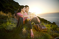 South Africa, couple drinking white wine at the coast at sunset - TOYF000708