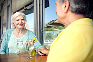 South Africa, happy senior couple holding hands in a cafe - TOYF000726
