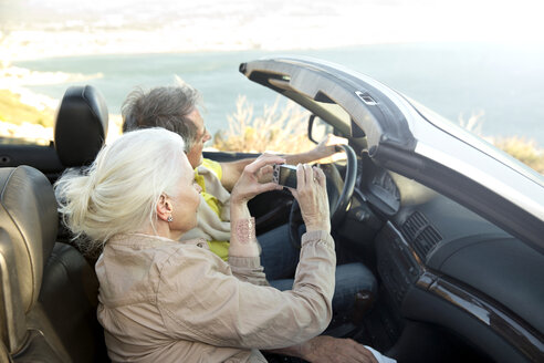 South Africa, senior couple sitting in a convertible looking at view - TOYF000719