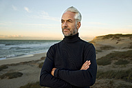 South Africa, portrait of white haired man wearing turtleneck standing on beach dunes before sunrise - TOYF000741