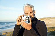 South Africa, portrait of white haired man with camera standing on beach dunes before sunrise - TOYF000744