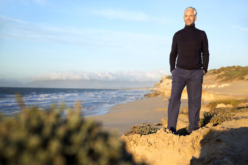 South Africa, man wearing turtleneck standing on rocks at the beach before sunrise - TOYF000747