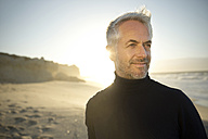 South Africa, portrait of white haired man wearing turtleneck standing on the beach  before sunrise - TOYF000753