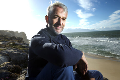South Africa, portrait of smiling man sitting on rocks at the beach - TOYF000762