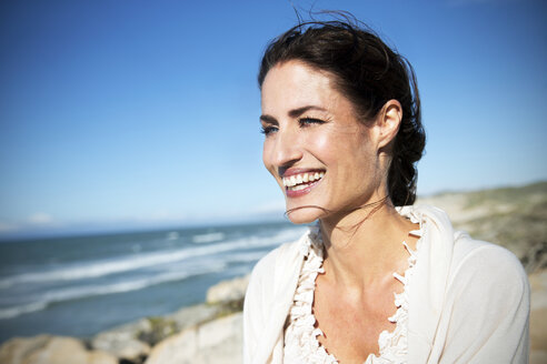 South Africa, portrait of smiling woman looking at the sea - TOYF000765