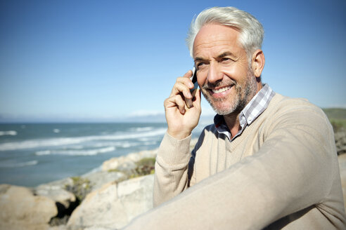 South Africa, portrait of smiling man sitting on rocks telephoning with smartphone - TOYF000807