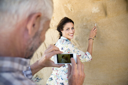 South Africa, man photographing his wife  carving something in a rock face - TOYF000782