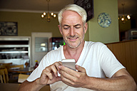 Portrait of smiling man sitting in a cafe using smartphone - TOYF000788