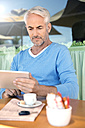 Portrait of man sitting in front of a cafe using digital tablet - TOYF000790