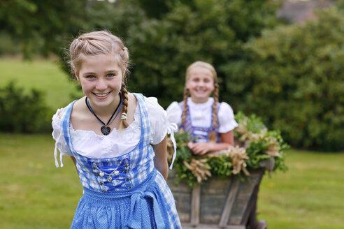 Germany, Luneburger Heide, portrait of smiling blond girl wearing dirndl pulling harvest wagon - HRF000029
