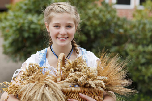 Germany, Luneburger Heide, portrait of smiling blond girl with basket of cereals - HRF000032