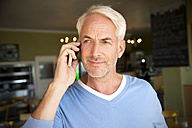 Portrait of white haired man telephoning with smartphone in a cafe - TOYF000809