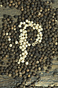 White peppercorns in between black peppercorns building the letter 'P' - ASF005597