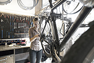 Young woman working in a bicycle repair shop - SGF001618