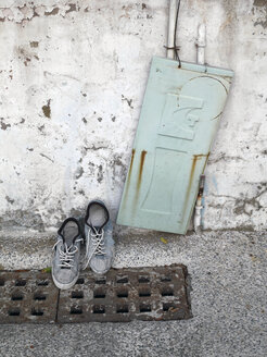 Taiwan, pair of shoes on gully cover and an old metal door leaning on a wall - JMF000346