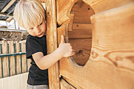 Little boy looking into a hole of wooden ship on playground - MFF001626
