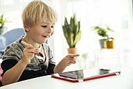 Happy little boy with digital pen and digital tablet at home - MFF001631