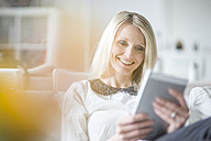 Portrait of smiling blond woman using mini tablet at home - CHPF000145