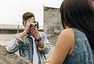 Spain, Gijon, young man taking pictures of his girlfriend with an old camera - MGOF000240