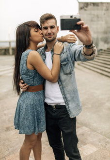 Spain, Gijon, young couple taking a selfie with an old camera - MGOF000241