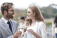 Couple toasting on terrace of a restaurant - ZEF005433