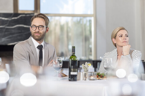 Mid adult couple at restaurant having communication problems - ZEF005160