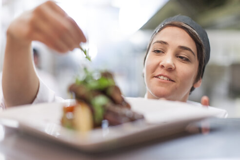 Young chef garnishing plate with food - ZEF005171