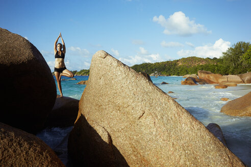Seychelles, woman standing on a rock doing yoga exercise - ABF000604