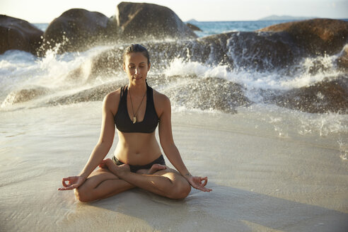 Seychelles, woman meditating at seafront - ABF000608