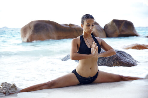 Seychelles, woman doing yoga exercise at seafront - ABF000621