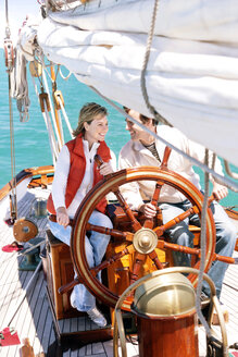 Happy mature couple at helm of a sailing ship - TOYF000821
