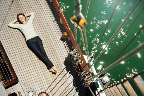 Relaxed mature woman lying on deck of a sailing ship - TOYF000823