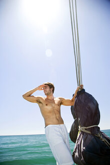 Young man on a sailing ship looking out - TOYF000859