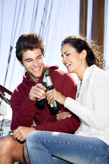 Happy young man and woman clinking beer bottles on a sailing ship - TOYF000885