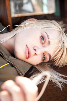 Relaxed young woman lying on a bench listening to music - TOYF000892