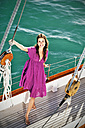 Smiling brunette young woman on a sailing ship - TOYF000922