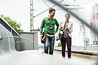 Young man and woman with cell phone on railway platform - UUF004492