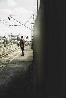 Young man with skateboard standing on railway platform - UUF004415