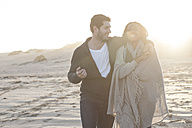 South Africa, Cape Town, young couple walking on the beach at sunset - ZEF005272