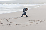 South Africa, Cape Town, man scratching heart in the sandy beach - ZEF005276