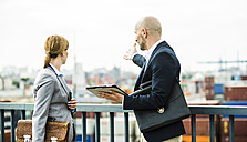 Businessman and businesswoman talking on bridge - UUF004431