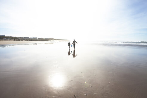 South Africa, Witsand, father and son walking on the beach at backlight - ZEF005305