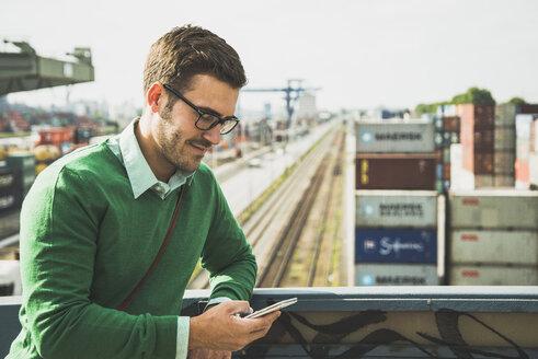 Man at freight yard looking at cell phone - UUF004442