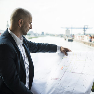 Businessman outdoors looking at construction plan at the river - UUF004494