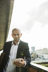 Confident businessman on bridge using digital tablet - UUF004446