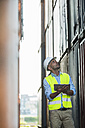 Man with digital tablet wearing reflective vest at container port - UUF004458