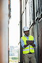 Man with digital tablet wearing reflective vest at container port - UUF004459