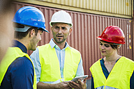 Woman and two men with safety helmets talking at container port - UUF004466