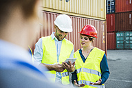 Woman and smiling man with safety helmets and digital tablet at container port - UUF004467